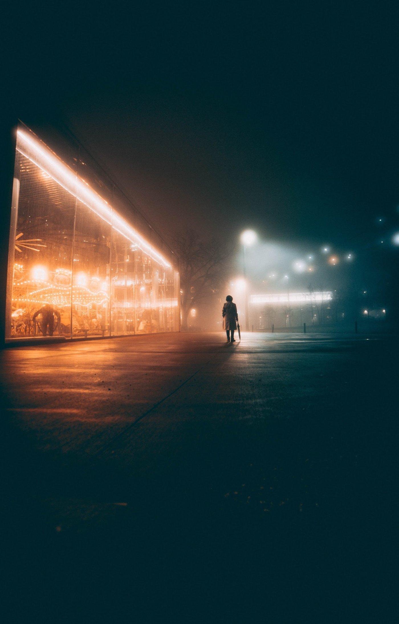 Une femme marche seule, de nuit, dans les rues de Paris.